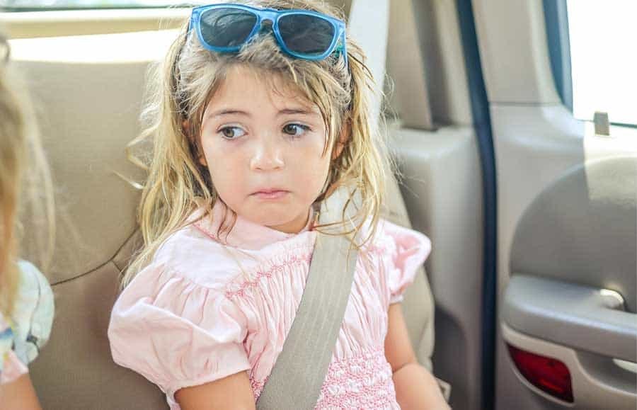 upset kid traveling in car